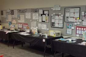 School projects displayed on table and wall